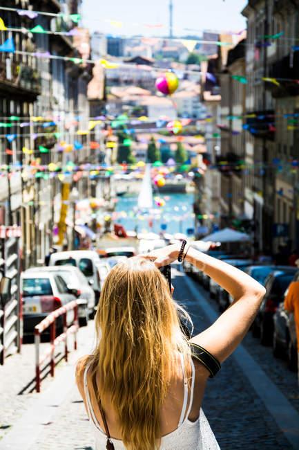 Vista posteriore di una donna bionda turistica scattare foto della città strada — Foto stock