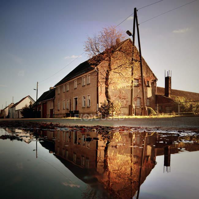 Лужа с отражением старого города зданий на поверхности воды — стоковое фото