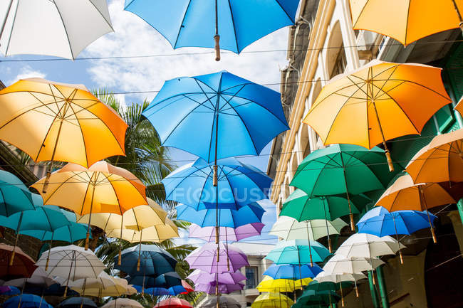 Colorful umbrellas hanging on wires in town — Stock Photo
