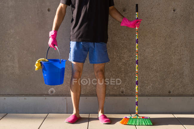 Man in colorful slippers wearing pink rubber gloves, holding blue plastic bucket, rags and broom — Stock Photo