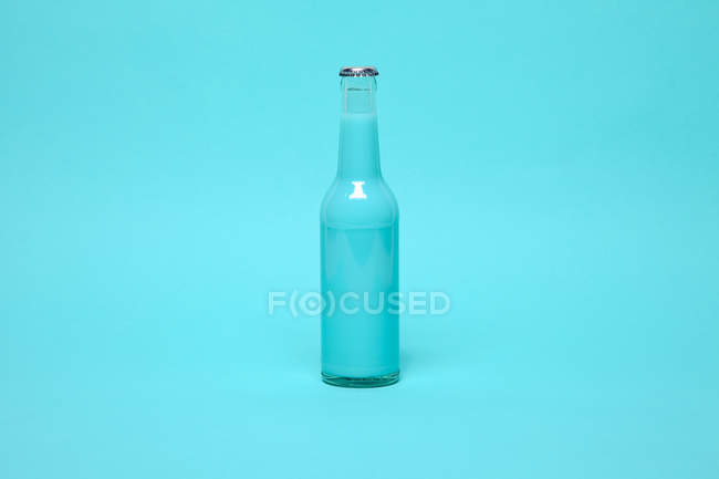 Bottle with drink on blue — Stock Photo
