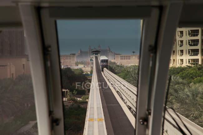 Route de chemin de fer avec le train dans la grande ville avec des bâtiments — Photo de stock