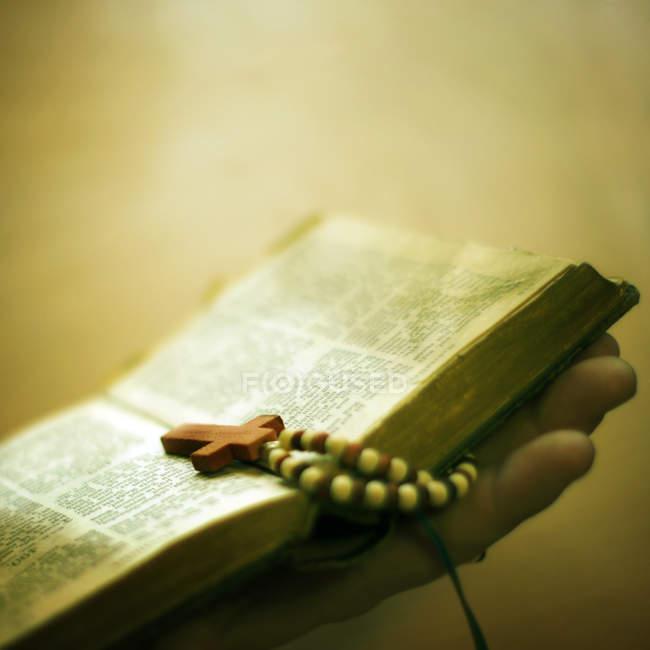 Vista do close-up de mão segurando a Bíblia e a Cruz — Fotografia de Stock