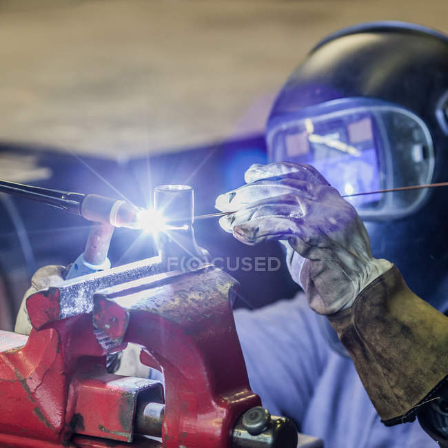 Welder in work process wearing safety helmet — Stock Photo