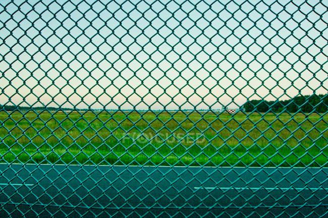 NET забор как поле барьер, зеленые линии границы на фоне — стоковое фото