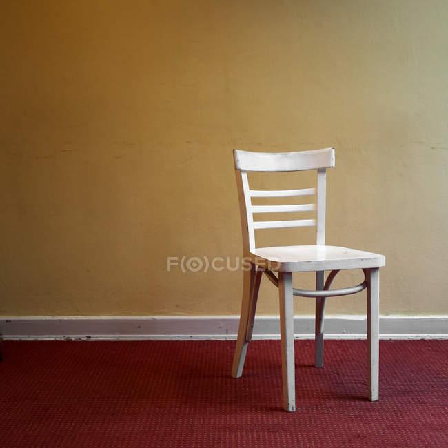 Cadeira de madeira branca vazia por parede amarela, design de interiores — Fotografia de Stock