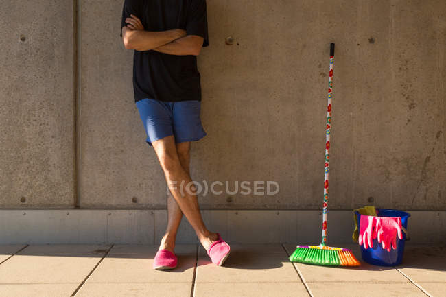 Man in colorful slippers wearing pink rubber gloves with arms crossed, blue plastic bucket, rags and broom by the wall — Stock Photo