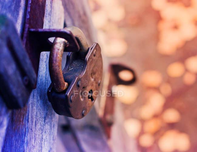 Locked rusty padlock hanging on wooden door — Stock Photo