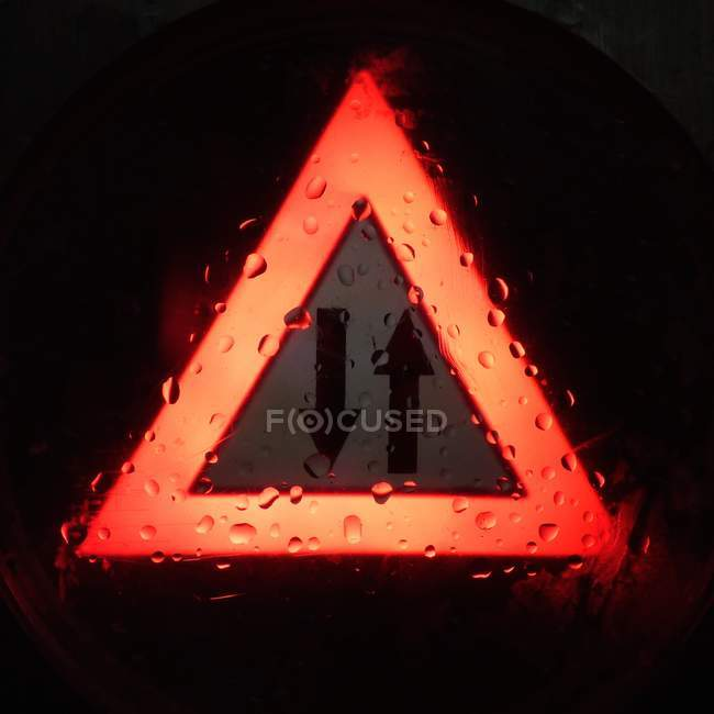 Two arrows signs in red illuminated triangle — Stock Photo