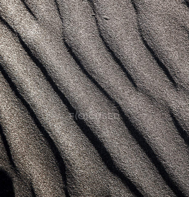 Dark grey sand surface with lines — Stock Photo