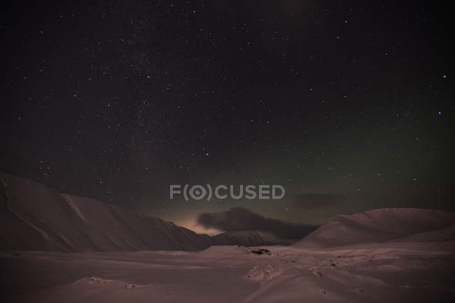 Twinkling stars in night sky above snow covered landscape with mountains hills — Stock Photo