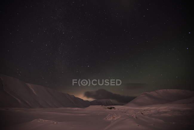 Мерцающих звезд в ночном небе выше снег пейзаж с холмами горы — стоковое фото