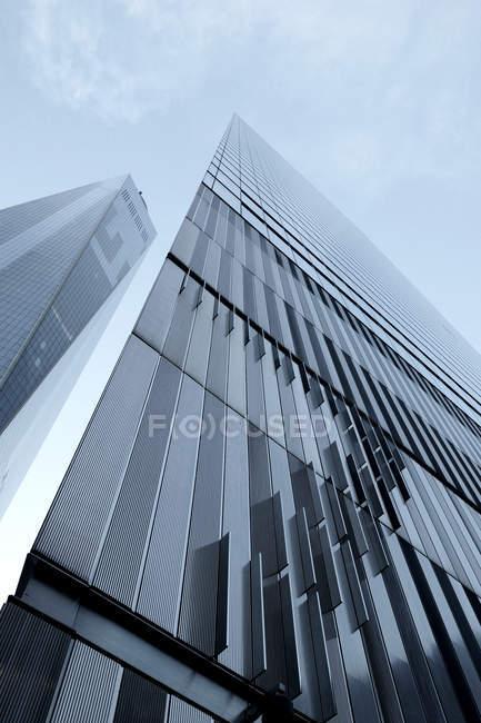 Vista inferior del moderno rascacielos con fachada de cristal en luz del sol - foto de stock