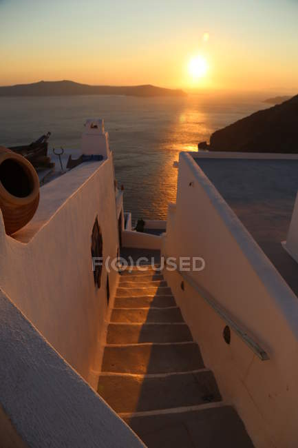 Sunset above sea, stairs between houses — Stock Photo