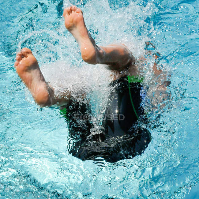Boy jumping in swimming pool blue water with splashes — Stock Photo