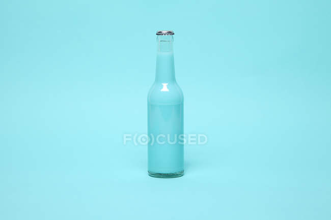 Glass bottle with blue cocktail drink — Stock Photo