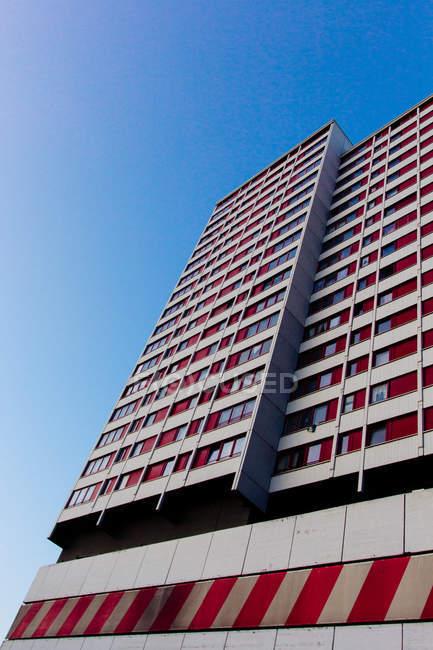 Edificio alto di facciata di architettura moderna contro il cielo blu, vista dal basso — Foto stock