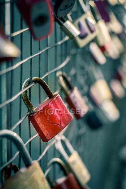Padlock with heart sign on fence — Stock Photo