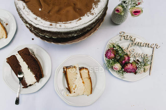 Different cakes on plates with flowers — Stock Photo