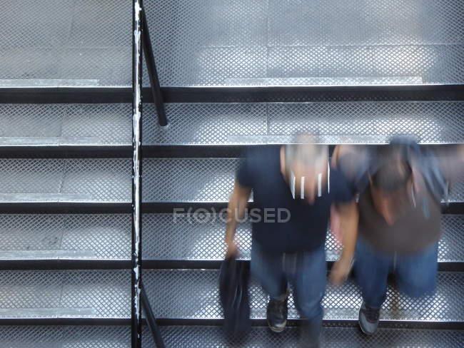 Мужчины в размытия движения пешком вниз по лестнице в подземном переходе — стоковое фото