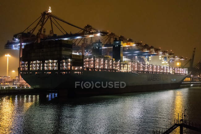 View of a huge cargo ship loaded with containers illuminated at night in harbor — Stock Photo
