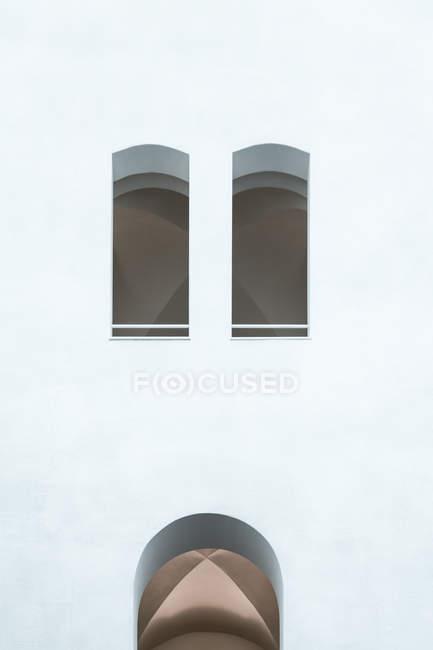 Colpo esterno della facciata dell'edificio bianco con finestre e arco — Foto stock