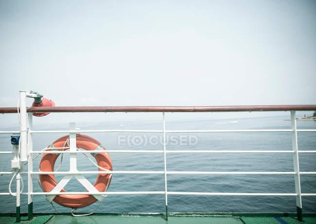 Pont de bateau avec bouée de sauvetage sur la balustrade, marine sur fond — Photo de stock
