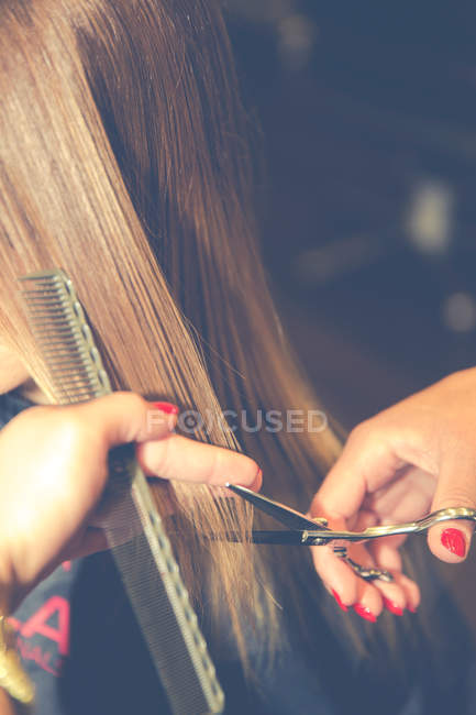 Cropped view of hairdresser cutting hair of female client — Stock Photo