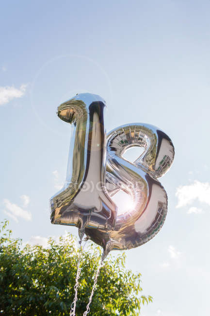 Silver inflatable number eighteen in sunshine against blue sky by green tree foliage — Stock Photo