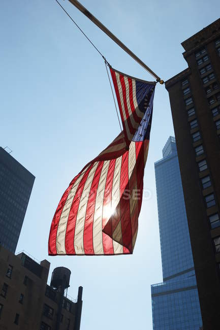 American flag waving among modern New York buildings in sunlight, USA — Stock Photo