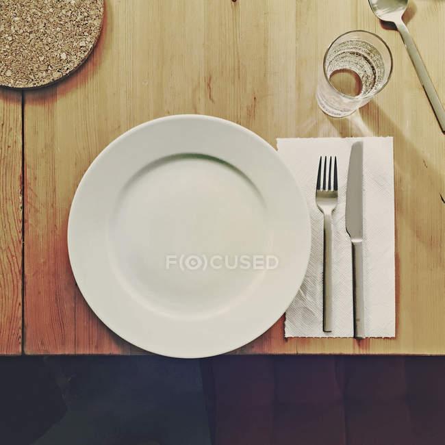Tavolo in legno con piastra, un bicchiere di acqua, forchetta e coltello — Foto stock