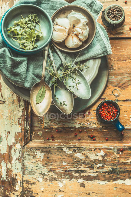 Top view of herbs and spices with vintage spoons on wooden table — Stock Photo