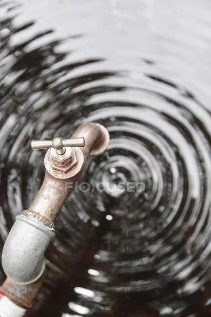 Vue du robinet métal avec gouttes de gouttes sur la surface de l'eau avec des cercles — Photo de stock