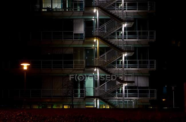 Темный фасад квартира в жилом районе города ночью — стоковое фото