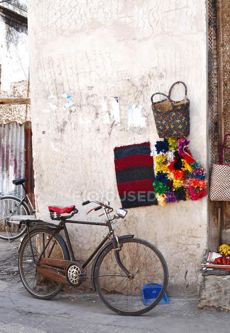 Tagsüber Blick auf Vintage Fahrrad geparkt in der Nähe von Mauerbau mit bunten Taschen und Dekorationen — Stockfoto