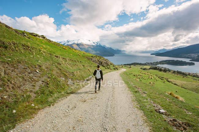 Viajante com mochila andando no caminho de montanhas de verão — Fotografia de Stock