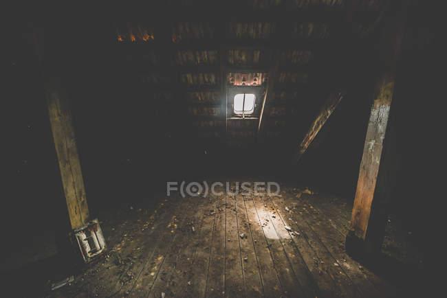 Wooden attic interior, light through window hatch — Stock Photo