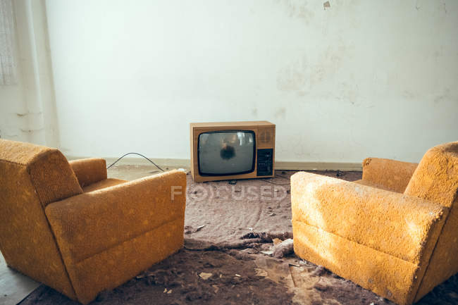 Broken vintage TV-set and two old armchairs in dirty room — Stock Photo