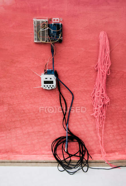 Closeup of electrical equipment and black wires on red wall — Stock Photo