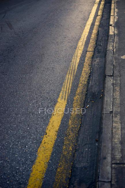 Des lignes jaunes sur la route goudronnée et margelle, plein cadre — Photo de stock