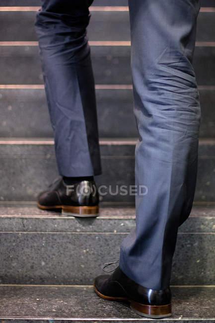 Recadrée vue des pieds d'homme d'affaires va à l'étage — Photo de stock