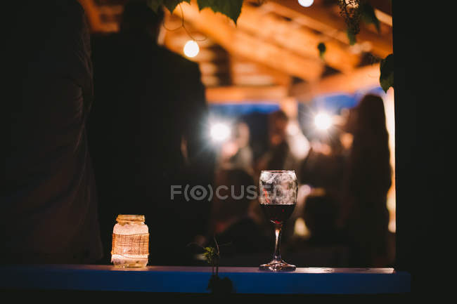 Glass of wine and candle on table at night party — Stock Photo