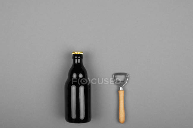 Glass bottle and opener on gray surface background — Stock Photo