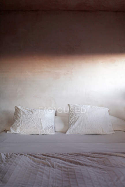 Daytime view of two white pillows on tidied bed indoors — Stock Photo
