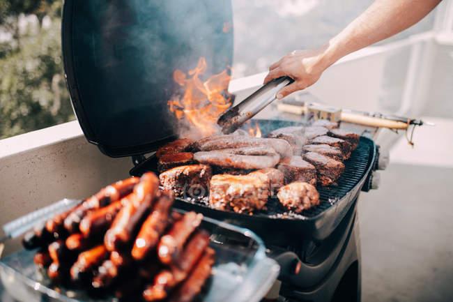 Человек приготовления сосиски на гриле — стоковое фото