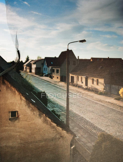 Village street with houses, view through fly protection screen — Stock Photo