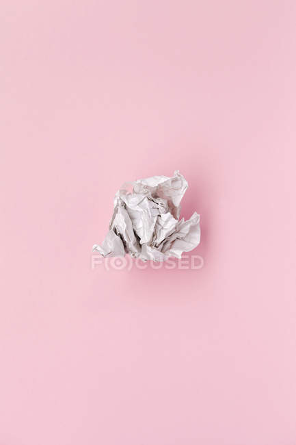 Crumpled piece of paper on pink background — Stock Photo
