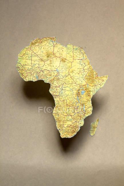 Schneiden Sie Teile der Karte repräsentieren Afrika Kontinent und Madagaskar Insel auf Beige Oberfläche — Stockfoto