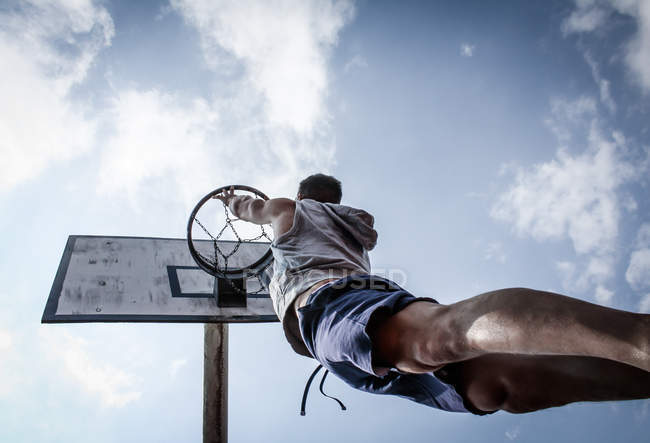 Skyward view of young man jumping reaching basketball basket — Stock Photo