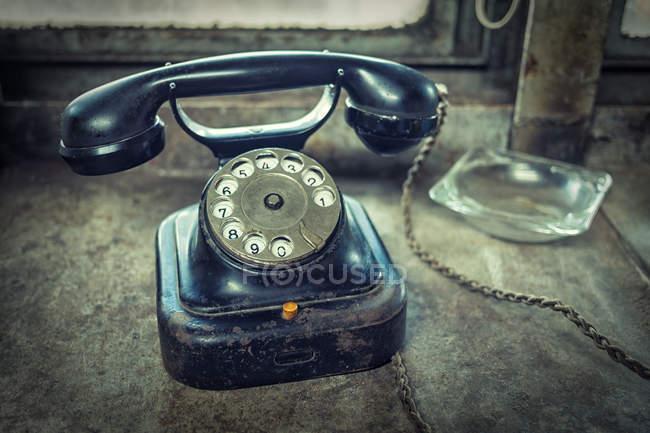 Blaue alte altmodisches Telefon mit Wählscheibe auf Tisch mit Glas Aschenbecher — Stockfoto